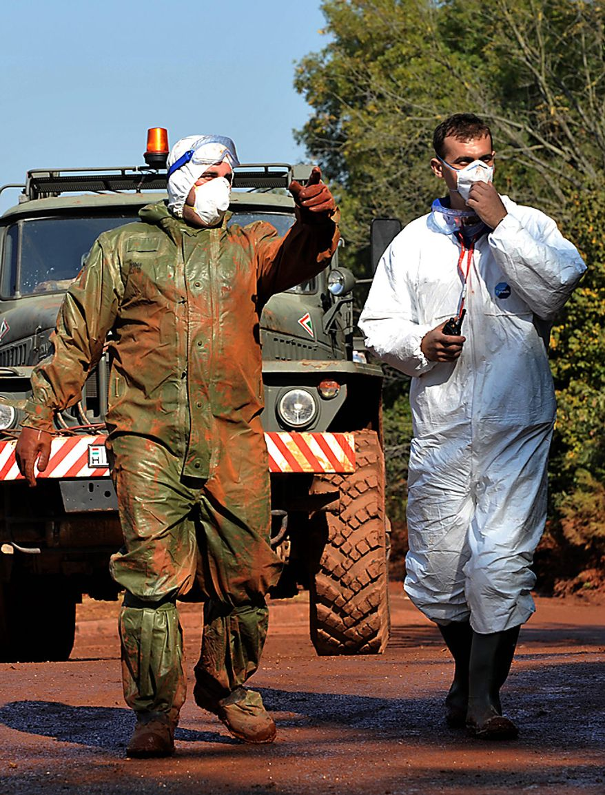 A Hungarian soldier and a volunteer, wearing protective gears, walk across a street covered by flooded toxic red sludge in Devecser, Hungary, Monday, Oct. 11, 2010. Hungary's prime ministers says police have taken into custody the managing director of the company which owns the metals plant where a broken reservoir flooded several towns with toxic red sludge and water.(AP Photo/Bela Szandelszky)