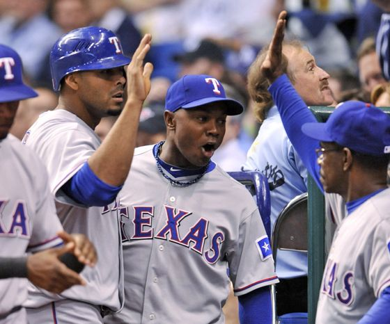 ASSOCIATED PRESS Texas Rangers manager Ron Washington, right, congratulates Nelson Cruz, left, who scored on a throwing error by Tampa Bay Rays  catcher Kelly Shoppach in the fourth inning during Game 5 of baseball's American League Division Series, Tuesday, Oct. 12, 2010, in St. Petersburg, Fla.