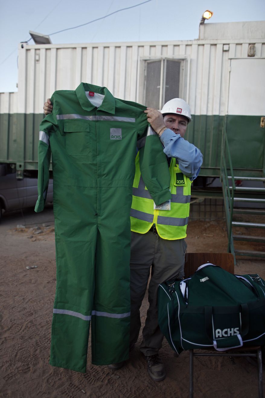On Monday, Oct. 11, 2010, a man working on the rescue of the 33 miners trapped at the San Jose mine near Copiapo, Chile, shows one of the pairs of overalls the miners will wear during their ascent to the surface. (AP Photo/Natacha Pisarenko)