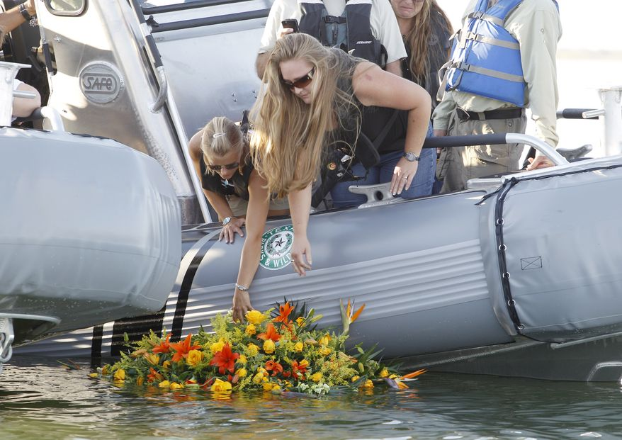 In this photo from Oct. 6, 2010, Tiffany Hartley (left) and family members lay a wreath near the site where her husband, David Hartley, was shot last month on Falcon Lake in Zapata, Texas. U.S. and Mexican authorities said Tuesday a Mexican state police commander investigating the Hartley's reported shooting and disappearance has been killed. (Associated Press)