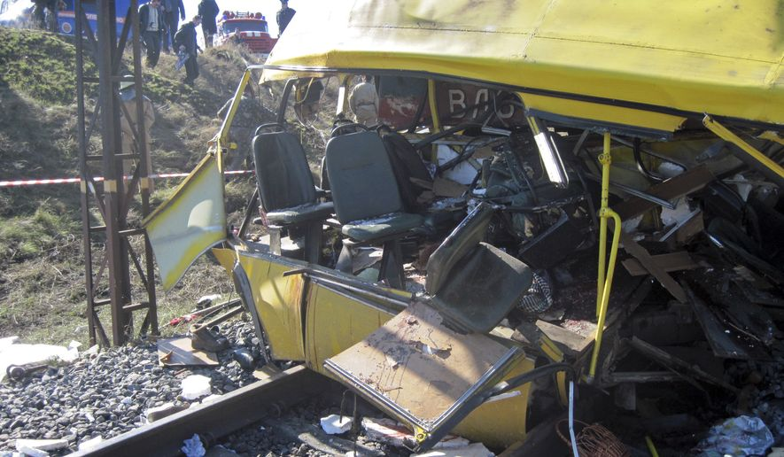 A train crashed into a bus outside Marhanets, Ukraine, on Tuesday, Oct. 12, 2010, when the bus driver attempted to cross the track after ignoring a warning siren from the locomotive and a red light that indicated an oncoming train. (AP Photo)