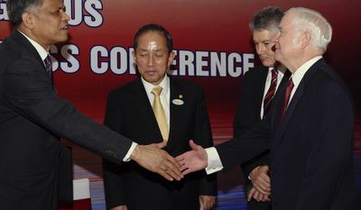 ASEAN Secretary General Surin Pitsawan (left) and U.S. Defense Secretary Robert M. Gates shake hands after the closing remarks of the ASEAN Defense Ministers' Meeting Plus in Hanoi on Tuesday, Oct. 12, 2010. (AP Photo/Luong Thai Linh, Pool)