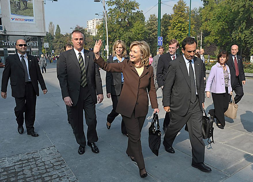 US Secretary of State Hillary Clinton, center, waves as she walks to a town hall meeting at the National Theater, Tuesday Oct. 12, 2010 in Sarajevo. Secretary Clinton arrived late on Monday, in the capital of ethnically divided Bosnia-Herzegovina, which just held elections, to urge the country's new leadership to make EU membership a priority (AP Photo/Mandel Ngan, Pool)