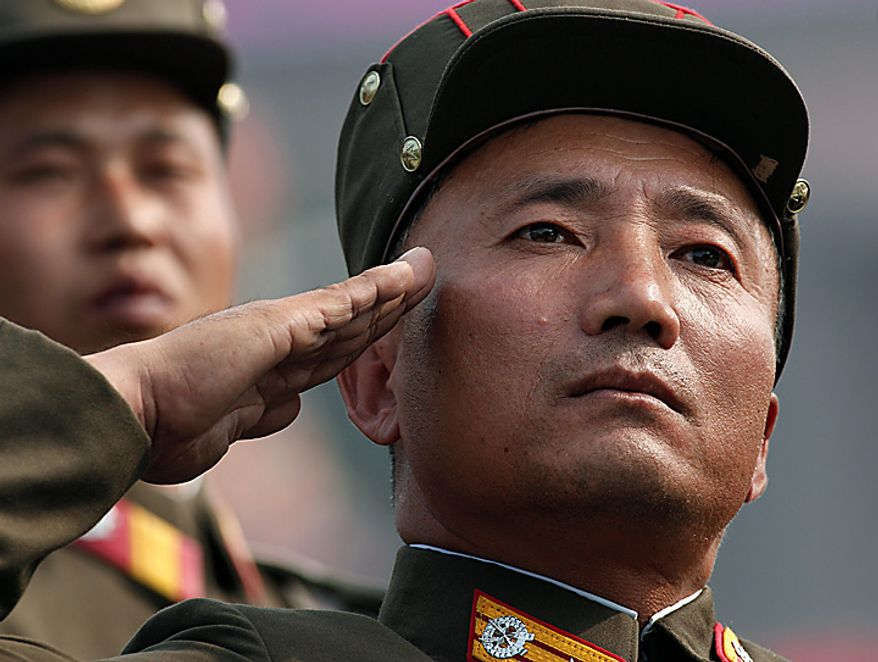 A North Korean soldier salutes as he marches in a massive military parade marking the 65th anniversary of the communist nation's ruling Workers' Party in Pyongyang, North Korea on Sunday, Oct. 10, 2010. This year's celebration comes less than two weeks after Kim Jong Il's re-election to the party's top post and the news that his 20-something son would succeed his father and grandfather as leader. (AP Photo/Vincent Yu)