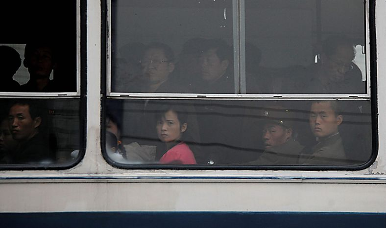 North Koreans look out from windows as they ride on a bus in Pyongyang, North Korea, Tuesday, Oct. 12, 2010. (AP Photo/Vincent Yu)