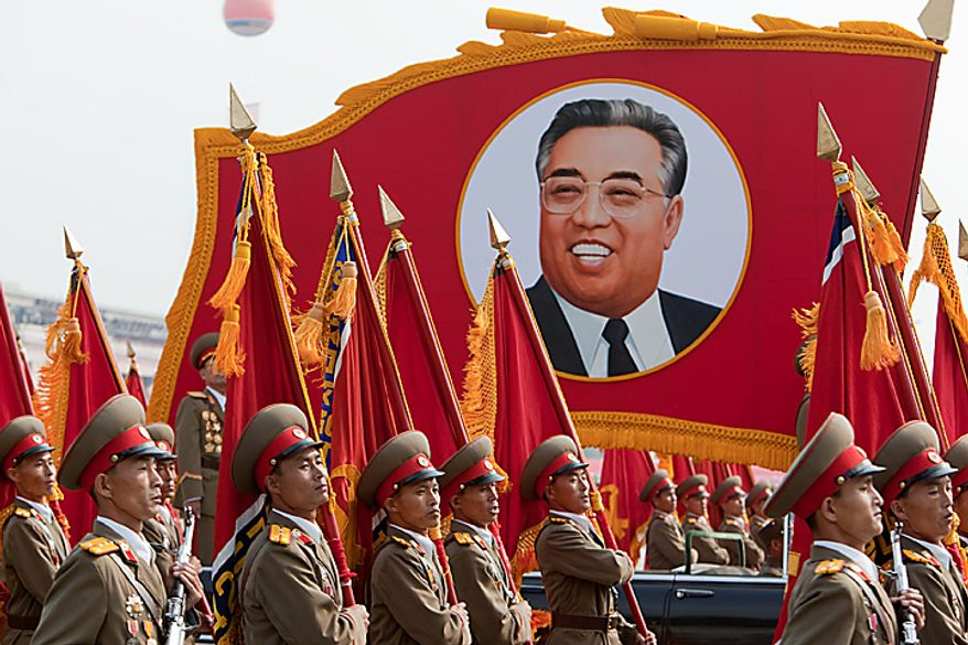 Members of the North Korean military march past a portrait of Kim Il Sung during a parade commemorating the 65th anniversary of the Korea Worker's Party in Pyongyang, North Korea, on Sunday, Oct. 10, 2010. North Korean heir apparent Kim Jong Un stood at his father's right side today as they reviewed troops, tanks and missiles in a Pyongyang military parade. Photographer: Dieter Depypere/Bloomberg