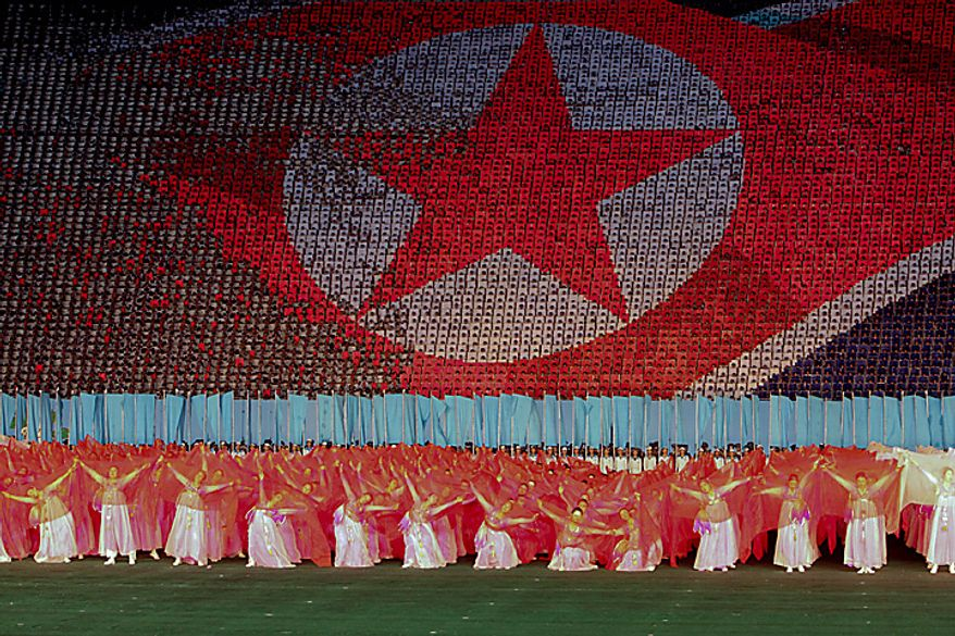 Performers dance in front of a depiction of the North Korean flag in Rungrado May Day Stadium during a ceremony commemorating the 65th anniversary of the Korea Worker's Party in Pyongyang, North Korea, on Saturday, Oct. 9, 2010. North Korean heir apparent Kim Jong Un stood at his father's right side today as they reviewed troops, tanks and missiles in a Pyongyang military parade. Photographer: Dieter Depypere/Bloomberg