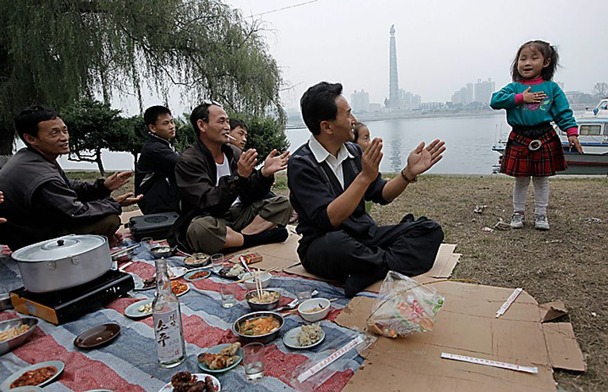 A North Korean girl sings as her family have a picnic along the Taedong River in Pyongyang, North Korea on Monday, Oct. 11, 2010. The party in Pyongyang stretched into Monday as North Koreans took the day off to celebrate a major political anniversary and to revel in the unveiling of leader Kim Jong Il's heir-apparent, son Kim Jong Un. (AP Photo/Vincent Yu)