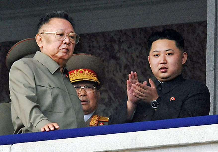 North Korea leader Kim Jong Il, left, walks by his son Kim Jong Un on the balcony as they attend a massive military parade marking the 65th anniversary of the communist nation's ruling Workers' Party in Pyongyang, North Korea on Sunday, Oct. 10, 2010. This year's celebration comes less than two weeks after Kim Jong Il's re-election to the party's top post and the news that his 20-something son would succeed his father and grandfather as leader. (AP Photo/Kyodo News)