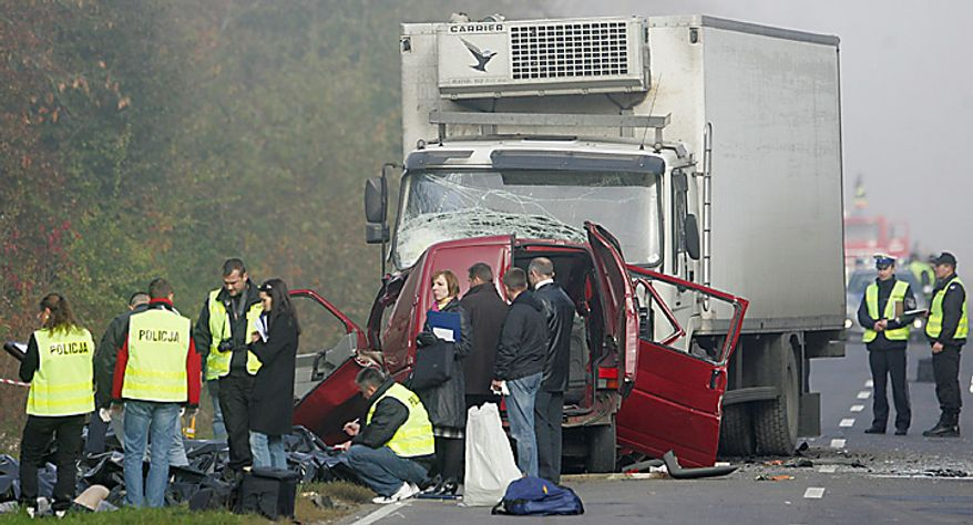 Police work at the site where a van carrying seasonal orchard workers crashed head-on with a truck while apparently trying to overtake in dense fog near Nowe Miasto in central Poland, killing all 17 passengers and the driver, early Tuesday, Oct.12, 2010. The truck driver was injured. (AP Photo)