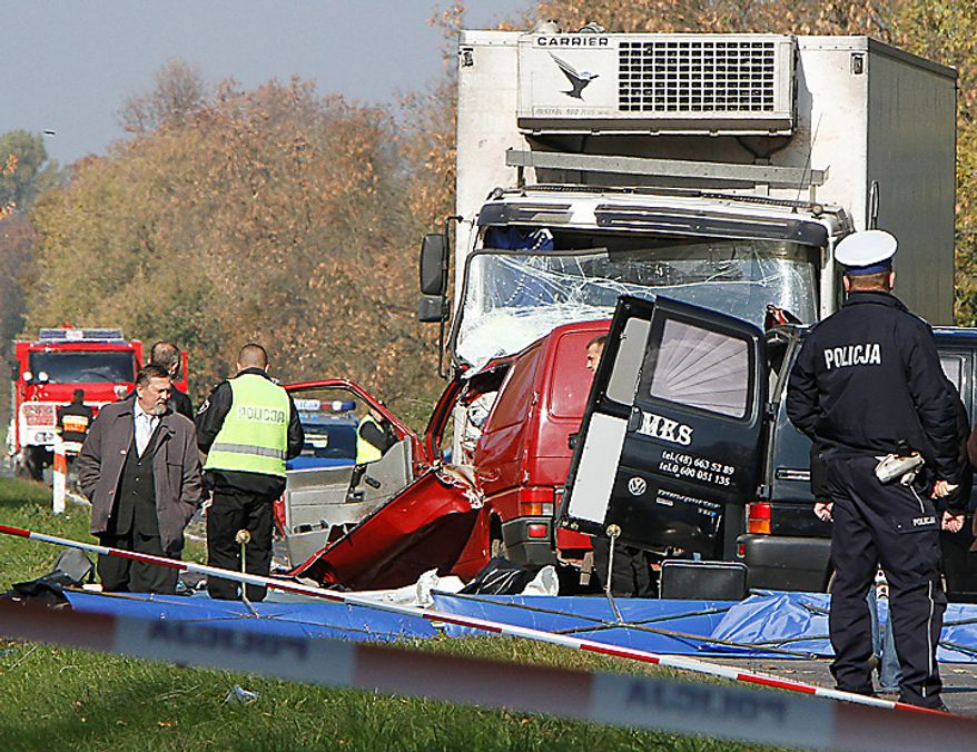Police stand next to the the wreckage of a van carrying seasonal orchard workers that crashed head-on with a truck while apparently trying to overtake in dense fog near Nowe Miasto in central Poland, killing all 17 passengers and the driver, early Tuesday, Oct.12, 2010. The truck driver was injured. (AP Photo/Czarek Sokolowski)