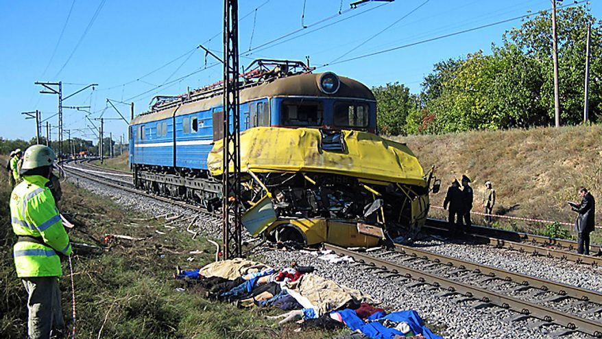 Victims bodies lie at the side of the track at the scene of an accident outside the town of Marhanets, Ukraine, Tuesday, Oct. 12, 2010 after the bus attempted to cross the track, ignoring a siren that indicated an oncoming train. At least 40 people were killed, officials at the Ministry of Emergency Situations said. Another eleven people were injured. Road and railway accidents are common in Ukraine, where the roads are in poor condition, vehicles are poorly maintained, and drivers and passengers routinely disregard safety and traffic rules. (AP Photo)