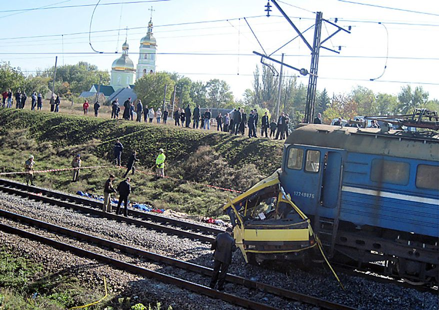 Victims bodies lie at the side of the track at the scene of an accident outside the town of Marhanets, Ukraine, Tuesday, Oct. 12, 2010 after the bus attempted to cross the track, ignoring a siren that indicated an oncoming train. At least 40 people were killed  officials at the Ministry of Emergency Situations said. Another eleven people were injured. Road and railway accidents are common in Ukraine, where the roads are in poor condition, vehicles are poorly maintained, and drivers and passengers routinely disregard safety and traffic rules. (AP Photo)