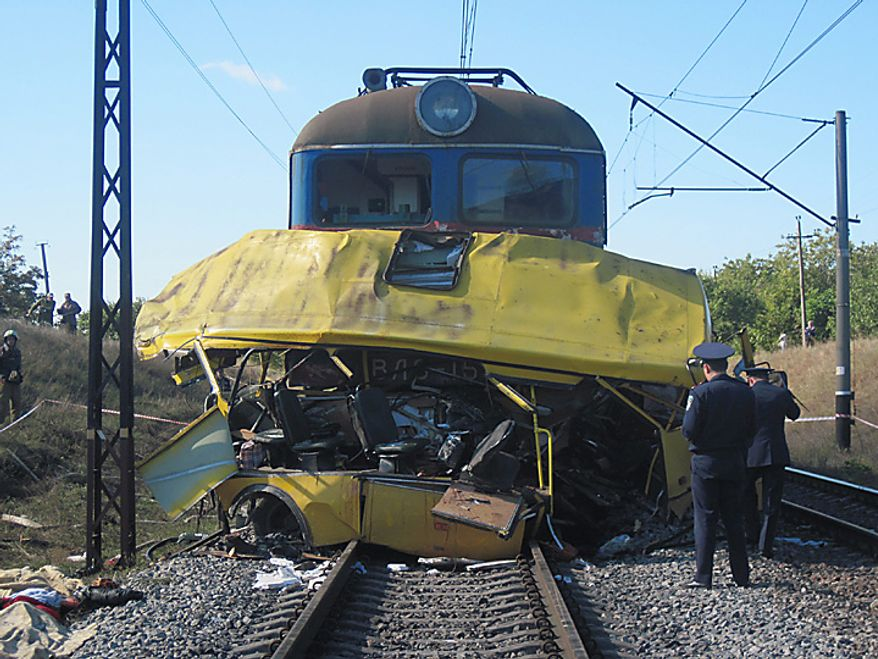 The remains of a bus lay next to a railway train at the site of an accident outside the town of Marhanets, Ukraine, Tuesday, Oct. 12, 2010. The crowded passenger bus collided with a train in eastern Ukraine Tuesday, killing 40 people and leaving 11 in critical condition, police said. The Interior Ministry said that the collision occurred outside the town of Marhanets in the Dnipropetrovsk region after the bus attempted to cross the track, ignoring a siren that indicated an oncoming train. Thirty-seven people from the bus died on the spot and another person died later in the hospital. There were no injuries reported on the train.(AP Photo/Emergency Situations Ministry)