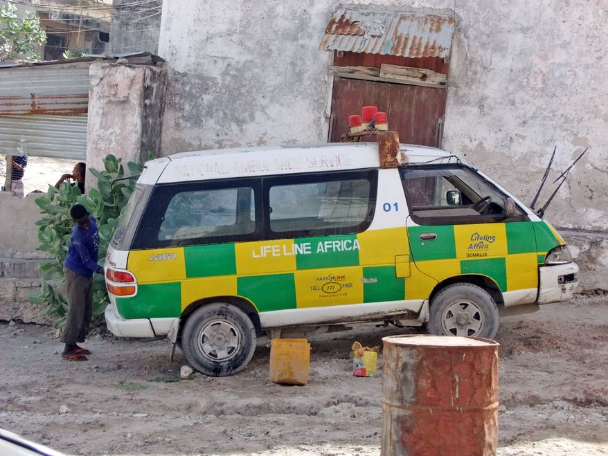 A boy hired to wash blood from an ambulance in Mogadishu, Somalia, won't be able to finish the job before its driver races off again to answer a call for help. (Associated Press)