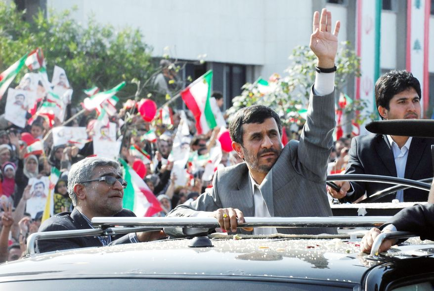 Iranian President Mahmoud Ahmadinejad waves to the crowds from the sunroof of his SUV, upon his arrival in Beirut on Wednesday. (Associated Press)