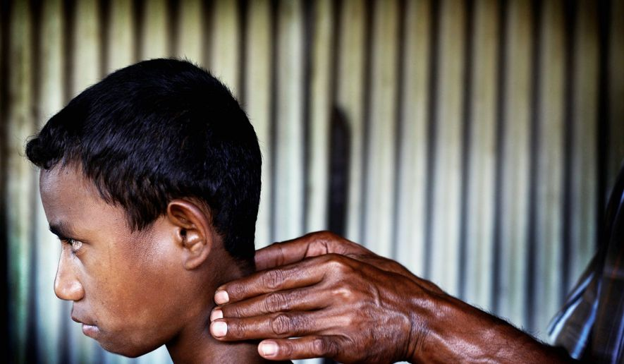 In Hauana, south of Oe-cusse town, East Timor, a boy suspected of being infected with leprosy is examined by a health official. East Timor is nearly within the World Health Organization's target for leprosy elimination, or less than one case per 10,000 people. (Associated Press)