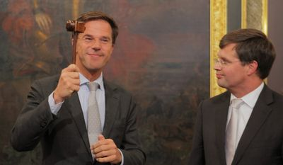 New Dutch Prime Minister Mark Rutte wields the gavel after receiving it from his predecessor, Jan Peter Balkenende, in The Hague on Thursday. Mr. Rutte's minority government pledged budgetary austerity and a crackdown on immigration. (Associated Press)