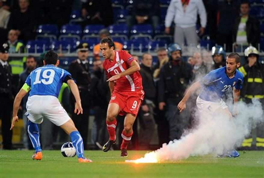 Italy's Gianluca Zambrotta, left, vies for the ball with Serbia's Dragan Mrdja and Italy's Leonardo Bonucci, right next to a burning flare thrown onto the pitch by Serbia supporters, not pictured, during the Group C, Euro 2012 qualifying soccer match between Italy and Serbia is suspended, at the Luigi Ferraris stadium in Genoa, Italy, Tuesday, Oct. 12, 2010. The Italy-Serbia European Championship qualifier was called off after seven minutes of play on Tuesday after Serbia fans threw flares and fireworks onto the pitch. (AP Photo/Fabio Ferrari, Lapresse)