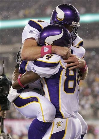Minnesota Vikings' Randy Moss, right, and quarterback Brett Favre celebrate after Moss caught a touchdown pass during the third quarter of an NFL football game Monday, Oct. 11, 2010, in East Rutherford, N.J. Favre became the first player in NLF history to throw 500 touchdown passes. (AP Photo/Kathy Willens)