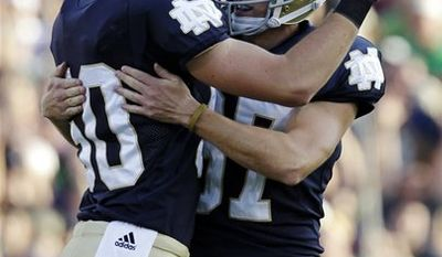 In this photo taken Saturday, Oct. 9, 2010, Notre Dame kicker David Ruffer, right, hugs holder Ryan Kavanagh after kicking a field goal against Pittsburgh during the second half of an NCAA college football game in South Bend, Ind. Ruffer is a former standout golfer who use to fling his clubs in anger. He's a transfer student, a walk-on and a former kicker in dormitory football. Now he's wearing the gold helmet of Notre Dame and so far, he's perfect on field goals _ 16-for-16, a school record.(AP Photo/Michael Conroy)