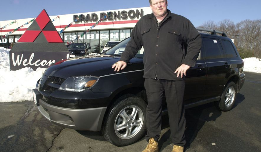 In this Feb. 20, 2003, file photo, car dealer Brad Benson, a former New York Giants center, stands in front of his car dealership in South Brunswick, N.J. The New Jersey car dealer who offered Florida pastor Terry Jones a new car if he promised to not burn a Koran plans to keep his word. (AP Photo, File)