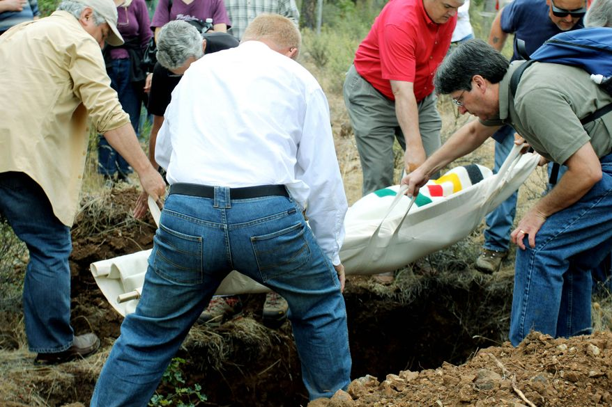 Friends and relatives carry Steve Sall's body to a grave at the White Eagle Memorial Preserve, a natural burial ground outside Goldendale, Wash. Sall, who died from complications from Lou Gehrig's disease, chose to be buried in this private forest. (Associated Press)