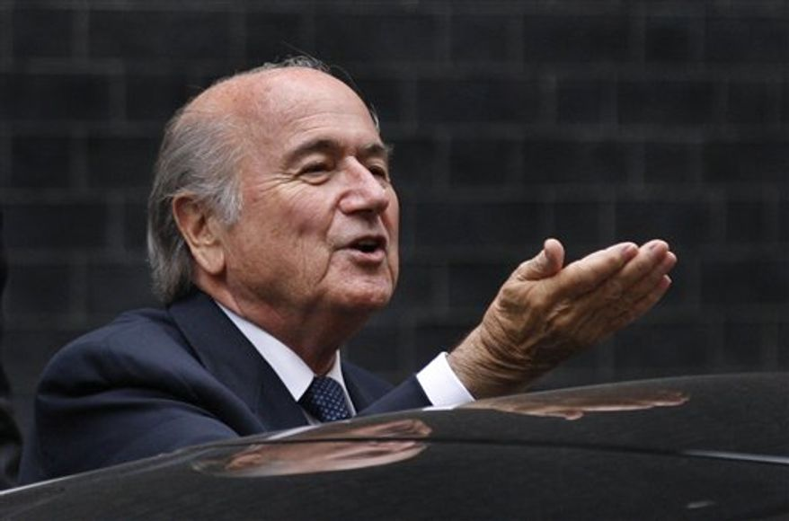 President of FIFA Sepp Blatter, second left, waves as he leaves 10 Downing Street in London after a meeting with British Prime Minister David Cameron over England's bid to host the 2018 soccer World Cup, Wednesday, Oct. 13, 2010. (AP Photo/Sang Tan)