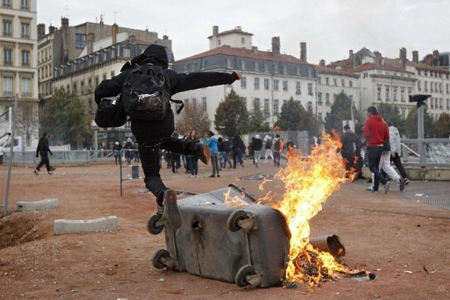 A protester jumps over a burning garbage can during clashes in Lyon, central France, on Tuesday. Some airliners steered clear of France and police clashed with stone-throwing youths Tuesday as a new round of nationwide strikes and protests over a bill raising the retirement age to 62 kicked off. (Associated Press)