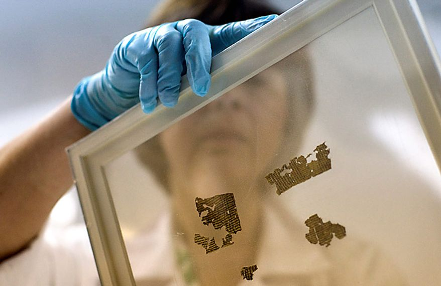 Lena Libman, a worker of the Dead Sea Scrolls conservation laboratory at the IAA,  Israel Antiquities Authority, holds a frame with small fragments of the Dead Sea Scrolls in a laboratory in Jerusalem, Tuesday, Oct. 19, 2010. Israel's Antiquities Authority and Google announced Tuesday they are joining forces to bring the Dead Sea Scrolls online, allowing both scholars and the general public widespread access to the ancient manuscripts for the first time. (AP Photo/Sebastian Scheiner)
