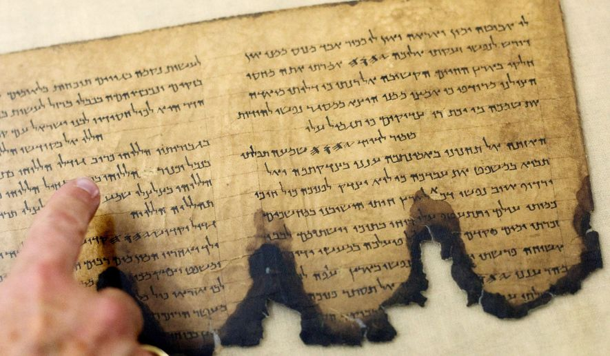 A worker at the Israel Antiquities Authority discusses one of the Dead Sea Scrolls, a collection of Hebrew, Aramaic and Greek documents found in Judean Desert caves in the 1940s. Google and the IAA plan to put them on a searchable database. (Associated Press)