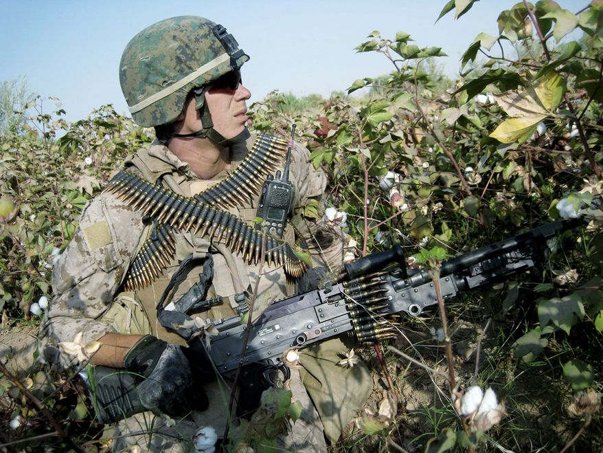 Marine Lance Cpl. Seth Little of Bremen, Ga., takes temporary cover in a cotton field during a patrol in Marjah, southern Afghanistan. The insurgents make their presence known but are hard to find. (Associated Press)
