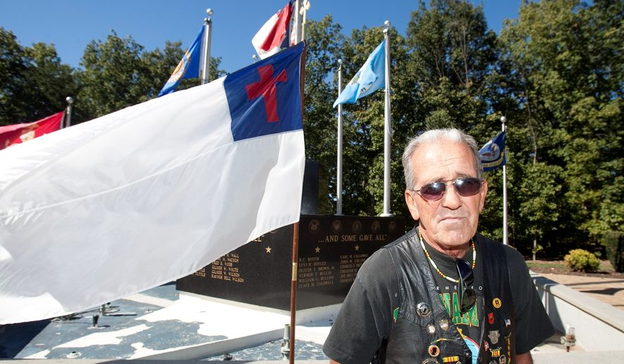 Air Force Vietnam veteran Ray Martini keeps vigil beside a new Christian flag put up in front of the memorial. (Associated Press)