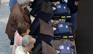 ASSOCIATED PRESS Election worker Laurnel Hoffman (upper right) helps voters to use the voting machines at an early voting polling place Saturday in Las Vegas.