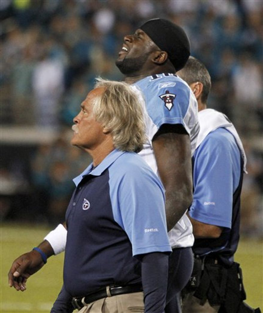 Tennessee Titans quarterback Vince Young grimaces as he walks off the field with trainers after he was injured during the first half of an NFL football game against the Jacksonville Jaguars in Jacksonville, Fla., Monday, Oct. 18, 2010. (AP Photo/Reinhold Matay)