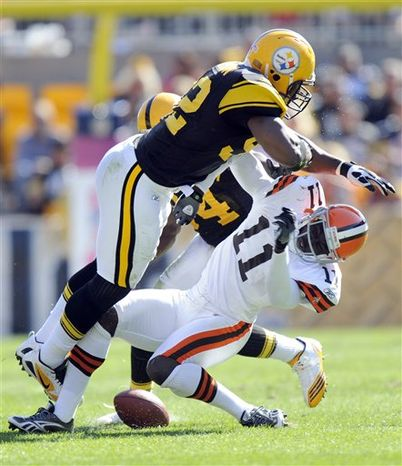 FILE - In this Oct. 17, 2010, file photo, Pittsburgh Steelers linebacker James Harrison (92) hits Cleveland Browns wide receiver Mohamed Massaquoi (11) during the second quarter of a an NFL football game in Pittsburgh.  Harrison was fined $75,000 on Tuesday, Oct. 19, 2010, for his hit against Massaquoi. (AP Photo/Don Wright, File)