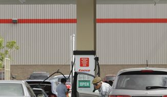 ASSOCIATED PRESS FILE In this Sept. 8, 2010 photograph, a Costco customer prepares to pump gasoline at a Costco in Redwood City, Calif.