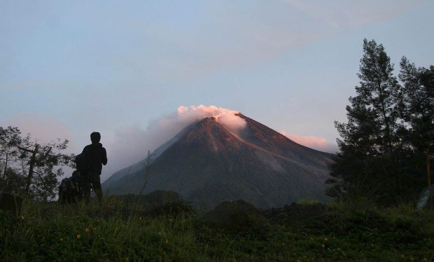 A villager watches Mount Merap in Indonesia. Scientists warned that mounting pressure could trigger the most powerful eruption in years. (Associated Press)