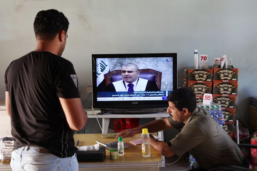 "Iraqis in a Baghdad cafe watch the sentencing of Tariq Aziz. Saddam Hussein's right-hand man was convicted of ""deliberate murder and crimes against humanity."" (Associated Press)"