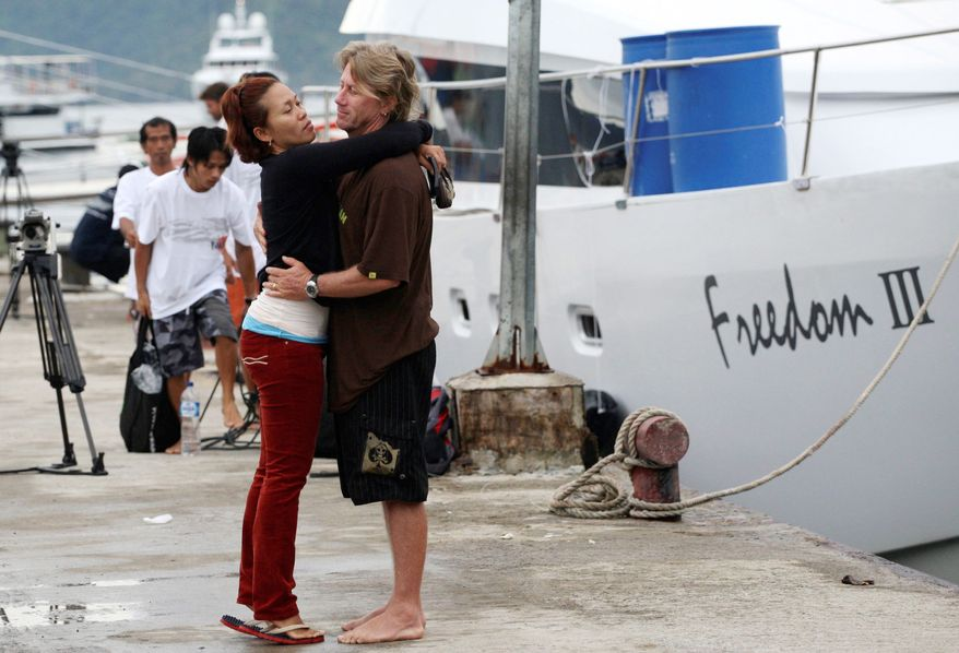 Tsunami survivor Rick Hallett, a boat captain, hugs his Indonesian wife, Hesti Dwiningsih, upon his arrival in Padang, West Sumatra, Indonesia on Wednesday. (Associated Press)