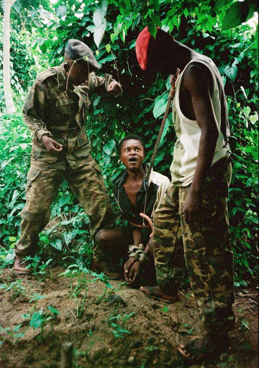 In May 1997, a Hutu refugee with his hands bound pleads for his life to two soldiers, whom the photographer identified as Rwandan Tutsis, about 30 miles south of Kisangani in Congo, then known as Zaire. The photographer said the soldiers killed him moments later. (Associated Press)
