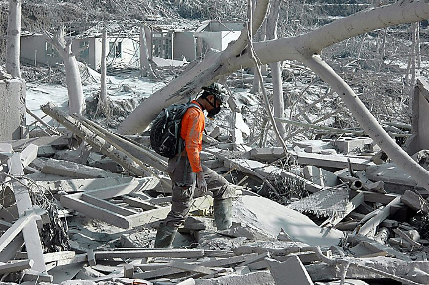 """A rescue worker searches for victims of Mount Merapi eruption at a village that is hit by pyroclastic flows in Kaliadem, Yogyakarta, Indonesia, Wednesday, Oct. 27, 2010. A volcanic eruption and a tsunami killed scores of people hundreds of miles apart in Indonesia, spasms from the Pacific """"Ring of Fire,"""" which spawns disasters from deep within the Earth. (AP Photo/Slamet Riyadi)"""