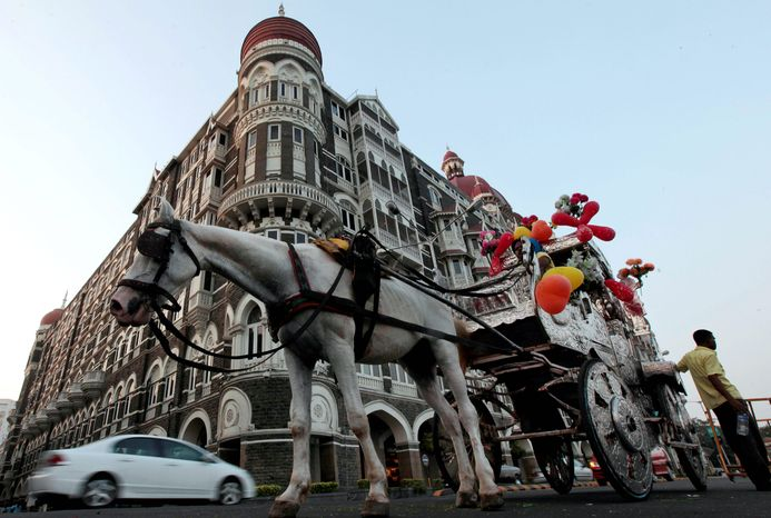 "A horse-drawn carriage awaits a rider in front of the Taj Mahal hotel in Mumbai on Thursday. President Obama is scheduled to stay at this hotel, which was the scene of one of the so-called ""26/11"" attacks. (Associated Press)"