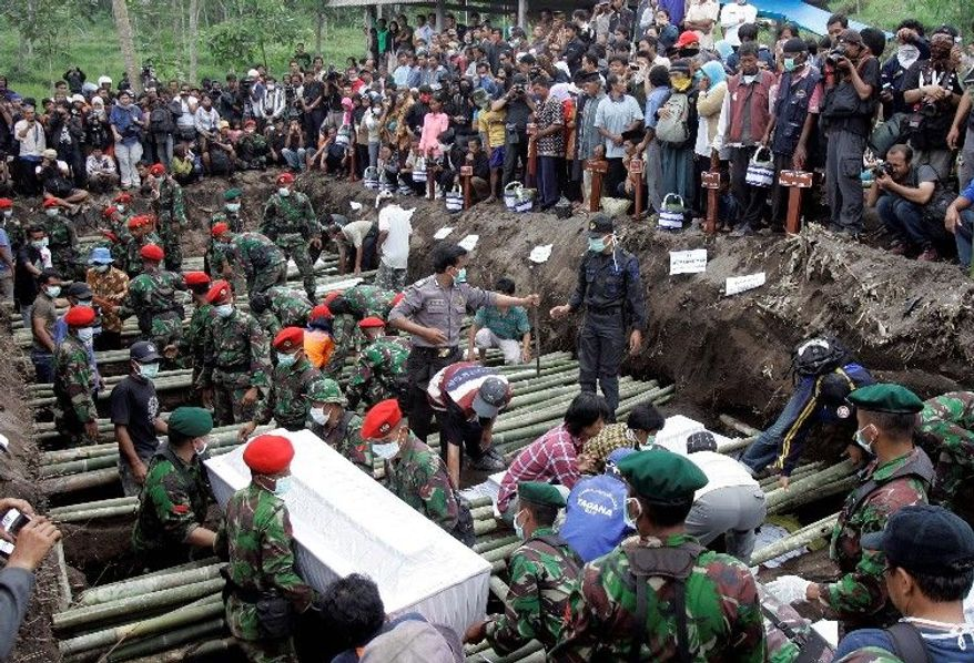 Soldiers carry the coffin of a victim of the Mount Merapi eruption at a mass burial Thursday in Umbulharjo, Indonesia. (Associated Press)