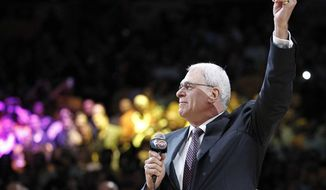 Los Angeles Lakers coach Phil Jackson holds up his NBA championship ring during a ceremony before the Lakers' basketball game against the Houston Rockets in Los Angeles, Tuesday, Oct. 26, 2010. (AP Photo/Chris Carlson)
