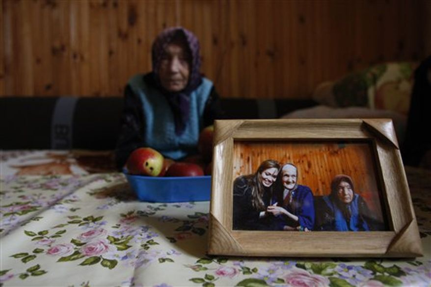 Bosnian Serb refugee Borka Mandzo, 68,with her nephew Nemanja, 6, right, and niece Natasa,13, left, reflected in a wall mirror sits in her small room , inside the collective refugee center in the Bosnian town of Rogatica, 73 kms east of Sarajevo, Bosnia, Monday, Oct. 25, 2010. The Babic sisters were among other 15 refugees visited in April 2010 by UNHCR goodwill ambassador Angelina Jolie. Refugees in Rogatica belong to population of 117.000 who were not able to return their homes 15 years after Bosnian war. Refugees in this center after Jolies visit are convinced that things have started moving in terms of getting some donation leading the solving their house problem.(AP Photo/Amel Emric)