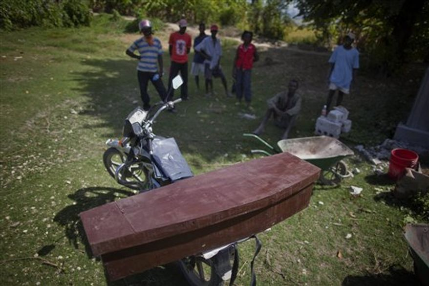 A woman holds a serum bag belonging to a patient with cholera symptoms being driven to a treatment center in Tabarre, on the outskirts of Port-au-Prince, Haiti, Wednesday Dec. 15, 2010.  (AP Photo/Guillermo Arias)