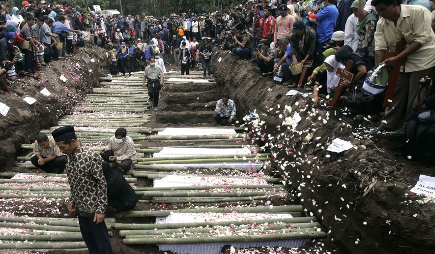 Relatives sprinkle flowers at the grave of the victims of Mount Merapi eruption during a mass burial in Umbulharjo, Yogyakarta, Indonesia, Thursday, Oct. 28, 2010. (AP Photo/Irwin Fedriansyah)