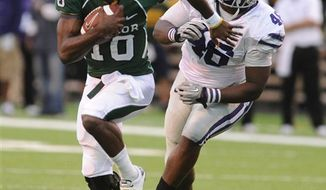 Baylor quarterback Robert Griffin, left, slips past Kansas State defensive tackle Prizell Brown during the first half of a NCAA football game, Saturday, Oct. 23, 2010, in Waco Texas. (AP Photo/Waco Tribune Herald, Rod Aydelotte)