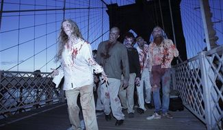 "A bicyclist and jogger pass a group of zombies posing for pictures on the Brooklyn Bridge in New York, Tuesday, Oct. 26, 2010.  The stunt was part of a campaign in 26 cities worldwide promoting the Halloween premiere of the AMC television series ""The Walking Dead."" (AP Photo/Seth Wenig)"